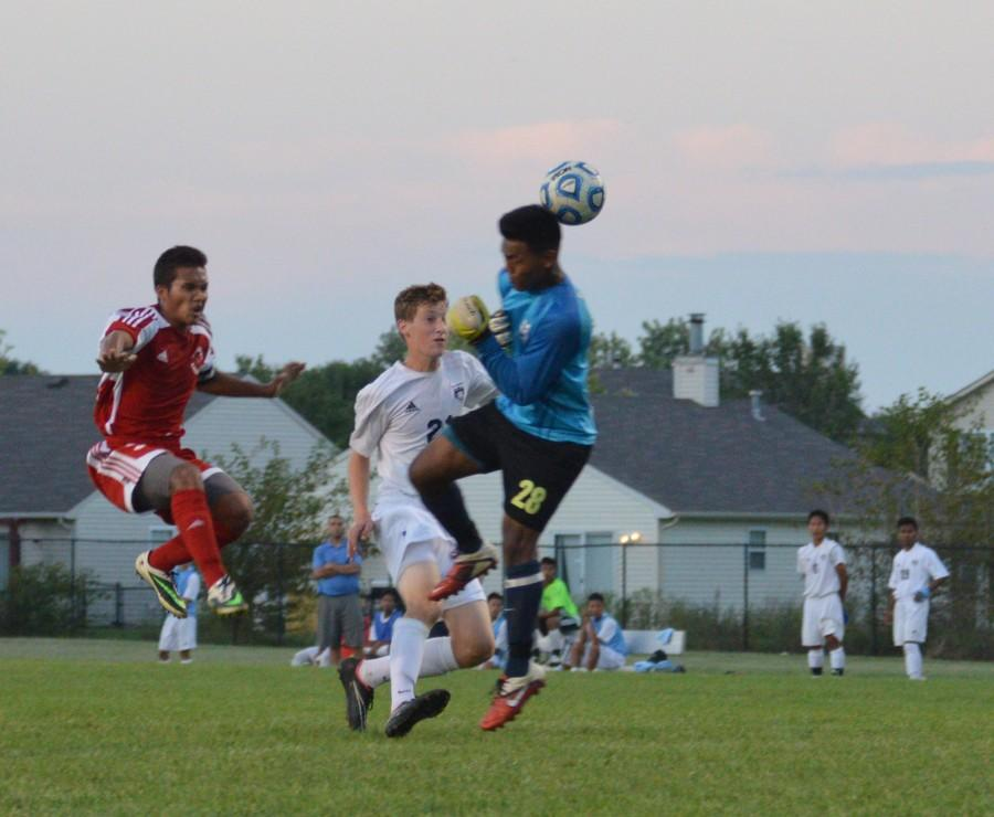 Senior Van Lian scores a goal over the Perry Meridian goalie's head. The Cardinals won the game, 3-2.