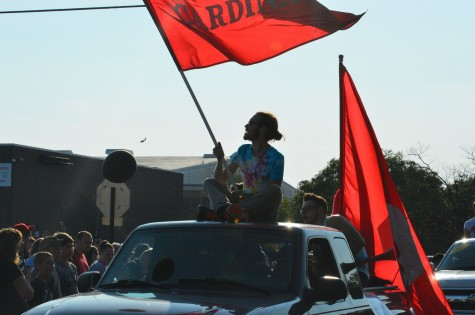 Senior Jake Rose holds a cardinal flag before the  beginning of a game on Sept. 19.