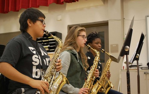 Melissa Navarro '17, Alaina Speiser '16, and Olatundun Awosanya '16 practice playing their saxophones in class. Saxophones are members of the woodwind family.