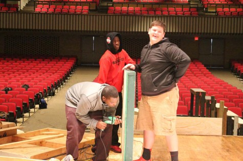 Eric Newton '15, Joshua Campbell '18 and Stephon Johnson '15 hold a platform to put wheels on. This platform was used for the moving sets in the plays.