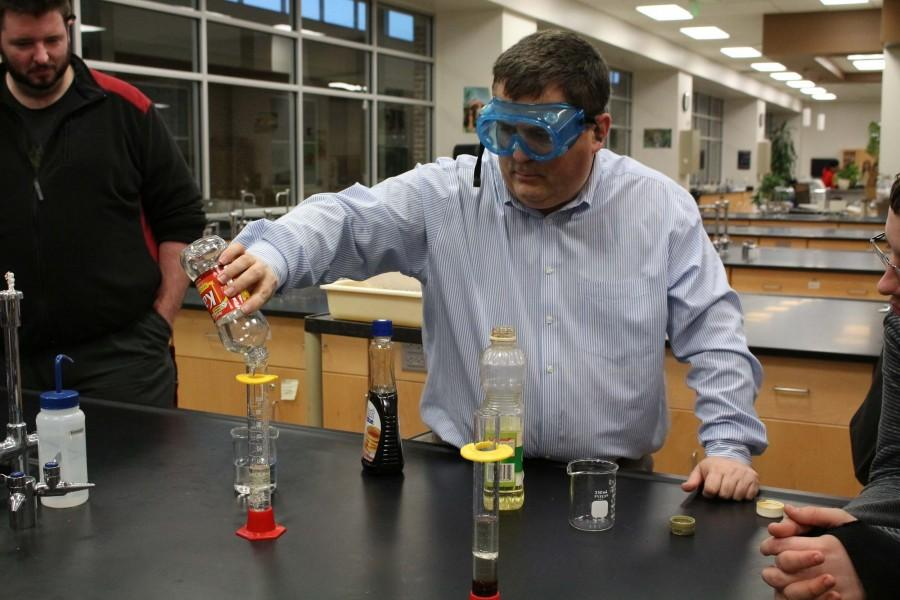 Science teacher Mr. Elmer Sanders mixes together substances to show the differences of density for a chemistry experiment on Jan. 22.