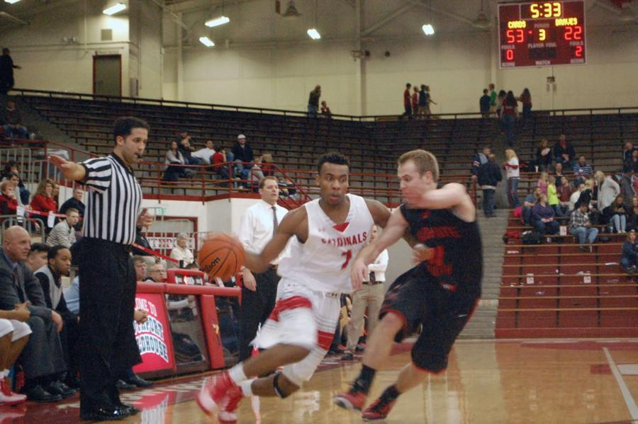 Sophomore Paul Scruggs drives to the basket with a defenders following him. Scruggs had 23 of his 25 points during the first half and contributed to the cards defense.