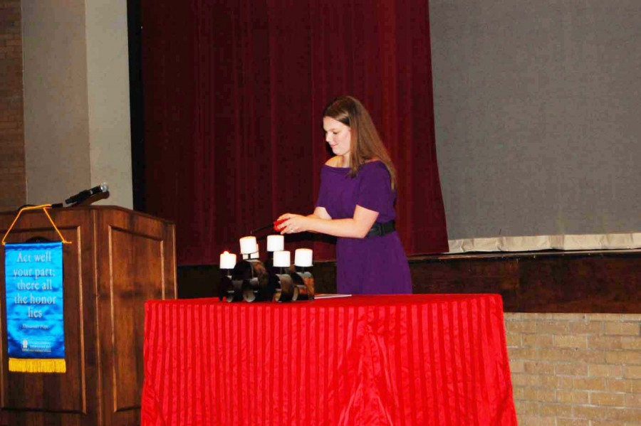 Senior Killian Nelson lights the third candle signifying the beginnings of music in theater. Nelson also spoke of her future plans to pursue music as a career.