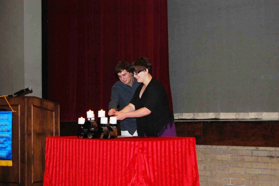 After speaking about dramatic literature, seniors Riley Owens and Cara Locke light the fifth candle as a pair. Owens was one of the 15 students inducted later that day.