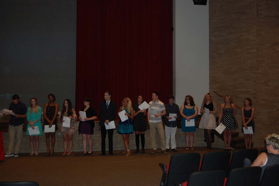 Fourteen of the 15 inductees stand across the front of the auditorium after they have been officially inducted. with their certificate signifying their life long membership as a thespian. Sophomore Keaton Moore, senior Riley Buckles, senior Micah harvey-King, senior Zuleima Reveles, senior Cara Locke, junior Nick May, senior Shayla Wright, senior Leigha Jones, senior Connor Moore, senior Riley Owens, senior Natalie Whitman,senior Isabella (___?__),  sophomore Madeline Hittle and sophomore Kendall March all hold their certificates that deem them thespians for the rest of their lives.