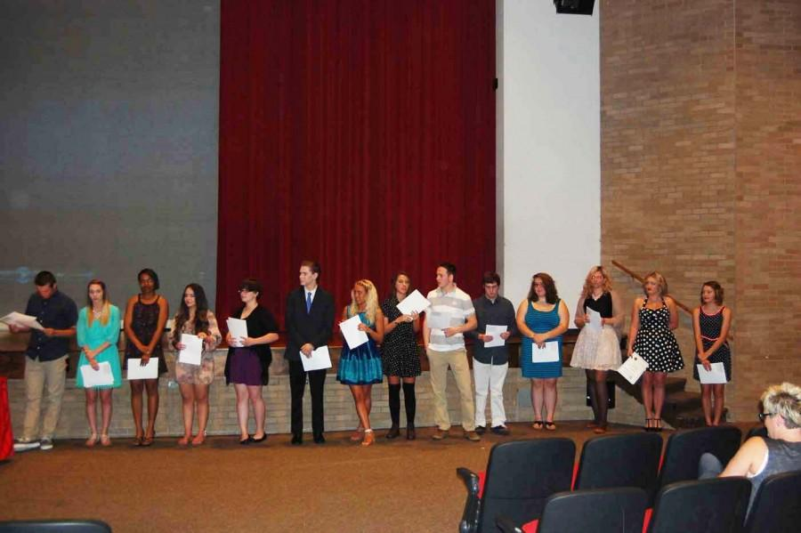Fourteen of the 15 inductees stand across the front of the auditorium after they have been officially inducted. with their certificate signifying their life long membership as a thespian. (from left to right) Sophomore Keaton Moore, senior Riley Buckles, senior Micah harvey-King, senior Zuleima Reveles, senior Cara Locke, junior Nick May, senior Shayla Wright, senior Leigha Jones, senior Connor Moore, senior Riley Owens, senior Natalie Whitman, senior Izabela Zbyrowska,  sophomore Madeline Hittle and sophomore Kendall March all hold their certificates that deem them thespians for the rest of their lives.