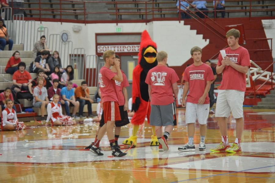 Booster Club members Cooper Davis, Joey Brunk, Trevor Coleman, and Shane Berch stand in the middle of the Fieldhouse alongside the Cardinal during the first pep-session on Aug. 21.