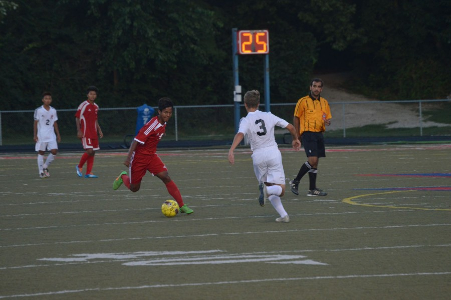 Senior Bawi Phutin tries to dribble past a Roncalli defender. Phutin is captain of the team.