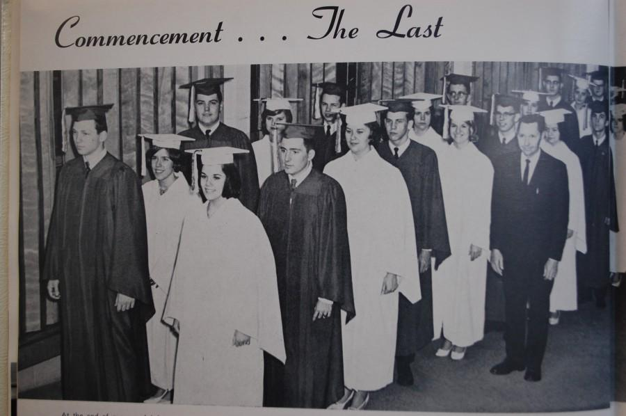 Graduates of the class of 1965 stand wearing their caps and gowns awaiting their turn to receive their diplomas.