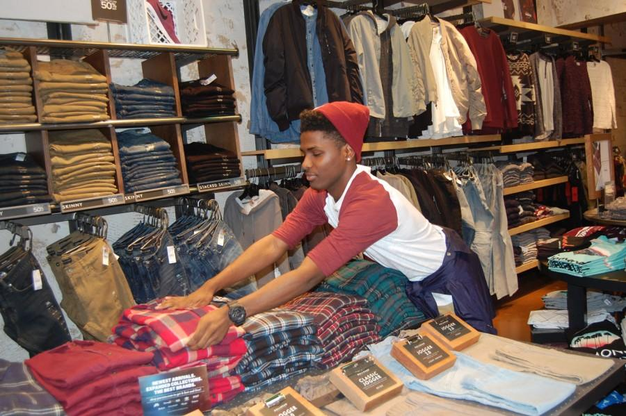 Junior Chaney Elliot folds flannels during work at Pac Sun on Friday Nov. 20.