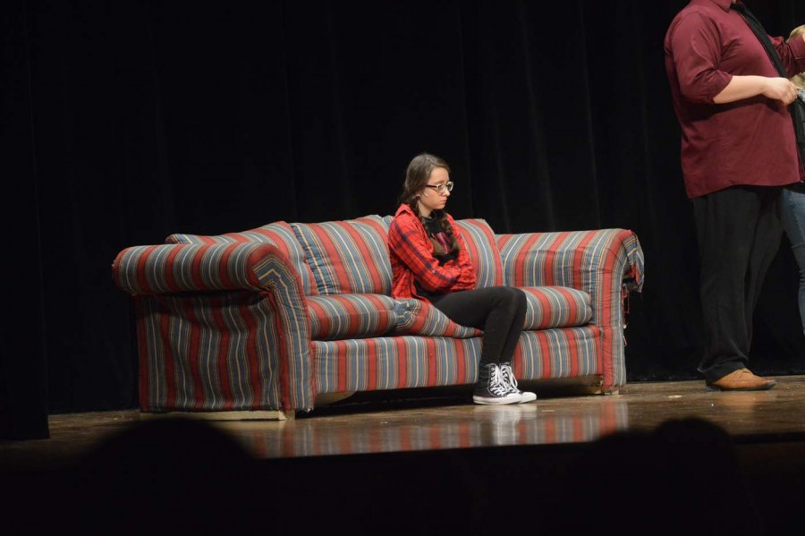"Freshman Maria Guia, playing the part of Audrey in ""Mr Winky: Murder at a Party,"" sits on a couch alone. Mr Winky: Murder at a Party was directed by seniors Taylor Staples and Sierra-Lynn Nolan."