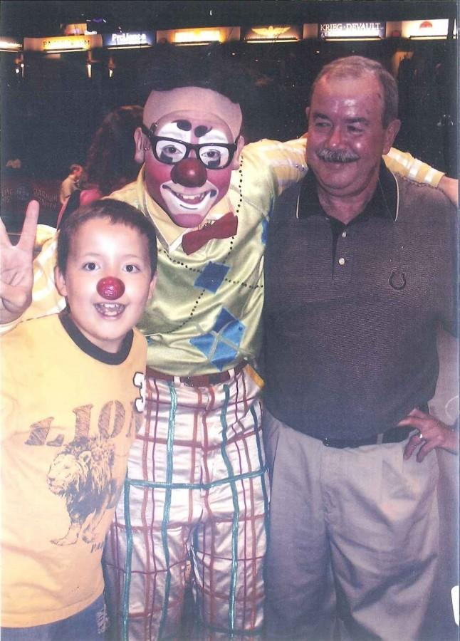 Marcos Valetin standing his grandfather and a clown.