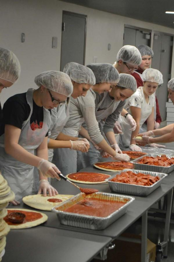 Pies are moving down the line as many RDM members do their job to make a perfect pizza.