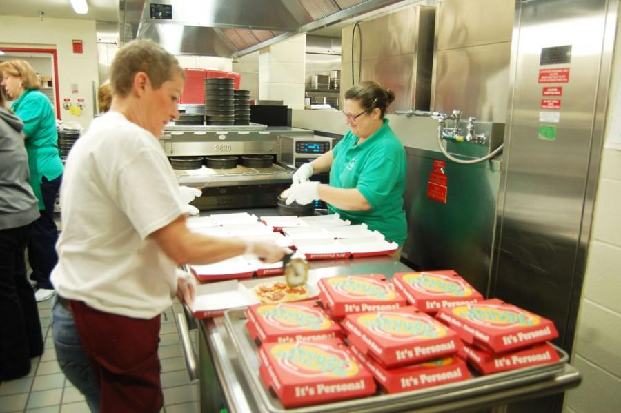 Kitchen staff members cut pizzas and put them in boxes on Feb. 4. They make pizzas four times a week.