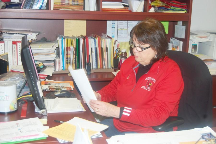 On Feb. 4, athletic secretary Peg Warner looks at paper work. One of Warner's jobs is to schedule games for sports.