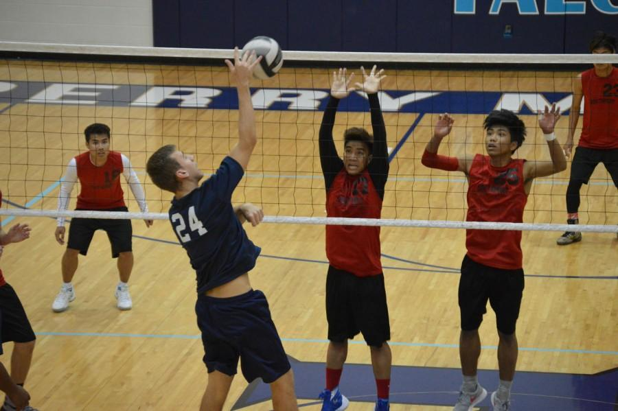 Senior Thawng Tha Bik and freshman Van Tin Thang jump to block a Perry Meridian player's spike. Bik and Thang are two out of six Chin students participating in boys volleyball this season.