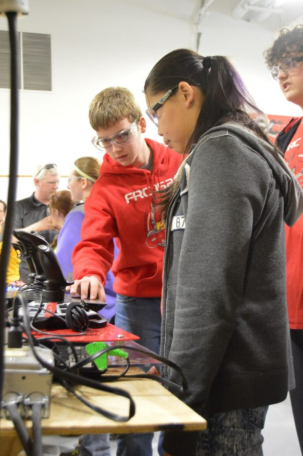 %28L+to+R%29+Freshman+John+Gunderson%2C+juniors+Zhu+Ling+Paige+and+Tyler+Hinton+prepare+the+controls+to+their+robot+before+a+competition.