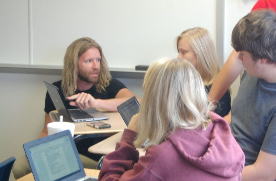 SHS teacher Christopher Sponsler aids students in a computer activity. He urges students to take a foreign language class, not just for communal purpose, but also to strengthen one's knowledge.