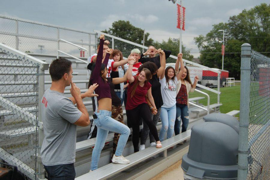 English teacher Brent Bockelman attempts to quiet down a group of freshmen who have arrived  two hours early to watch the football team practice.