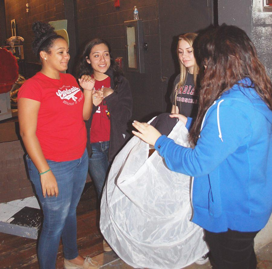 (left to right) Juniors Kayleon Boyd, Alex Castro, Natalie Sankey and Senior Nathaly Hernandez discuss the use of part of a prop while the cast is rehearsing on stage.