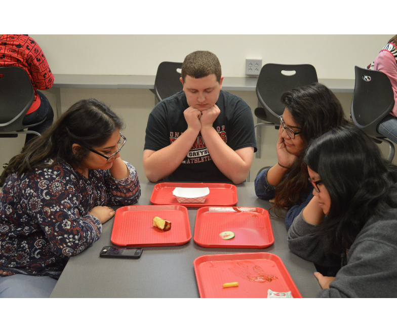 Students sit in silence with their nearly-empty lunch trays out in front of them. This picture was taken seconds before these students started fighting over who could eat the paper food boat.