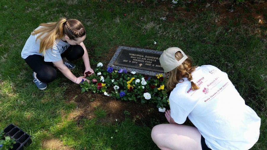 SMS student Cecelia Dunn and sophomore Abby Dunn lay flowers at their mother's grave. Both they and their brother Torey have now lost both of their parents.