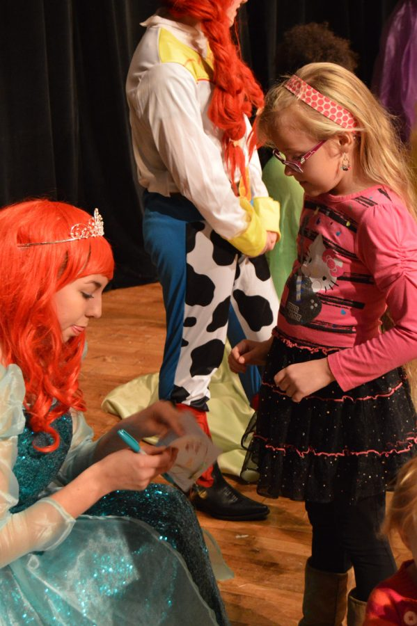 Sophomore+Aubrey+Popovic%2C+dressed+as+Ariel%2C+signs+an+autograph+book+for+a+girl.+Each+autograph+book+had+a+page+reserved+for+each+princess+to+sign.