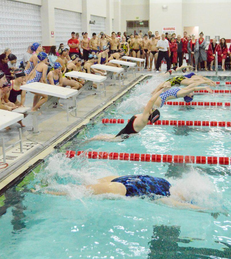 Sophomore Jordan Cox launches off the wall to swim backstroke at the Cardinal Classic on Dec. 3. Cox's current best backstroke time is 1:24:57.