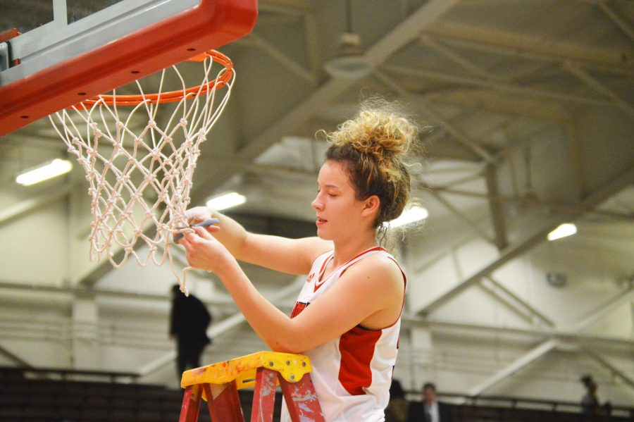 Senior Emma DeHart cuts down her piece of the basketball net after the conference basketball game on Jan. 26.  Dehart has been a part of the girls basketball team all four years of her high school career.