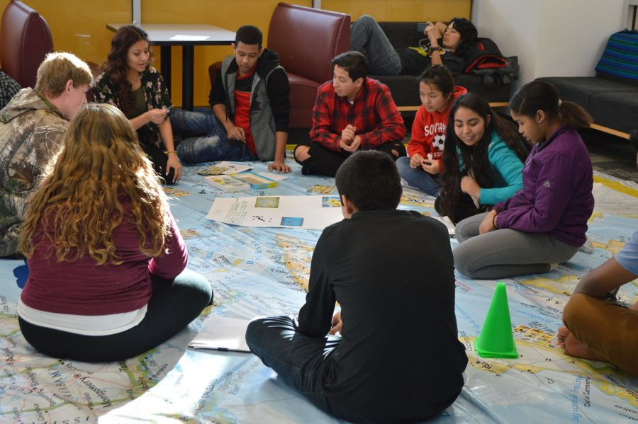 SHS students sit near the map and conversate about different countries. They talk about where they are from.