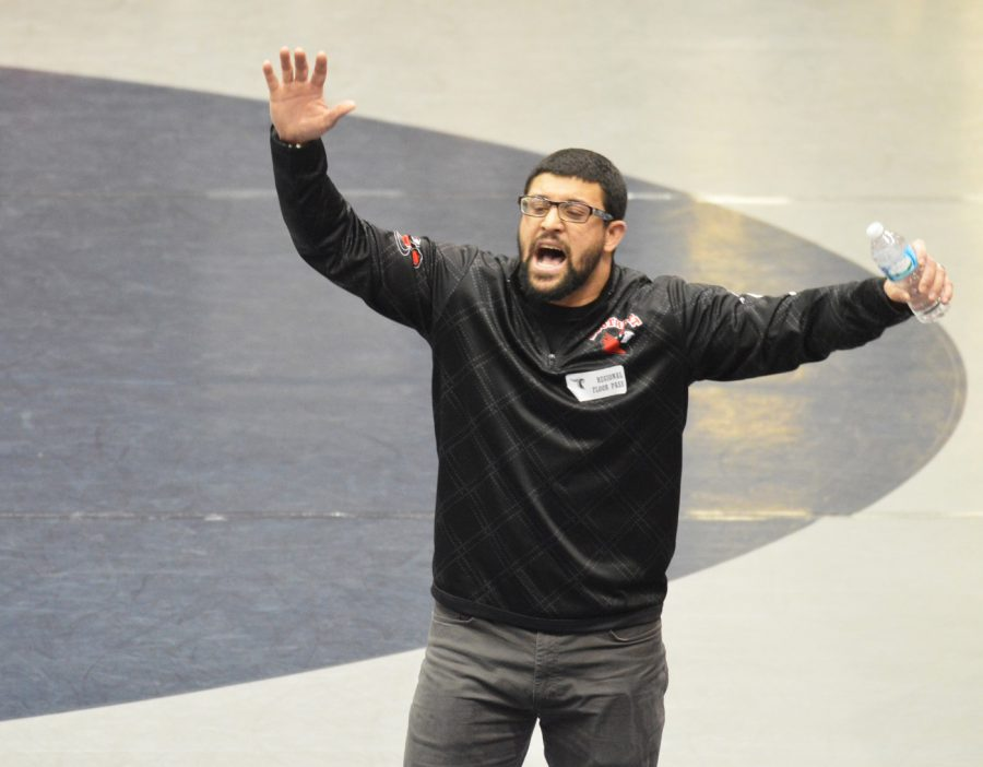 """Coach Albert Skinner yells """"heavy hands"""" at junior Dayton Fries during Regionals. Skinner is a first year coach at SHS, but has been a head coach of wrestling for six years."""