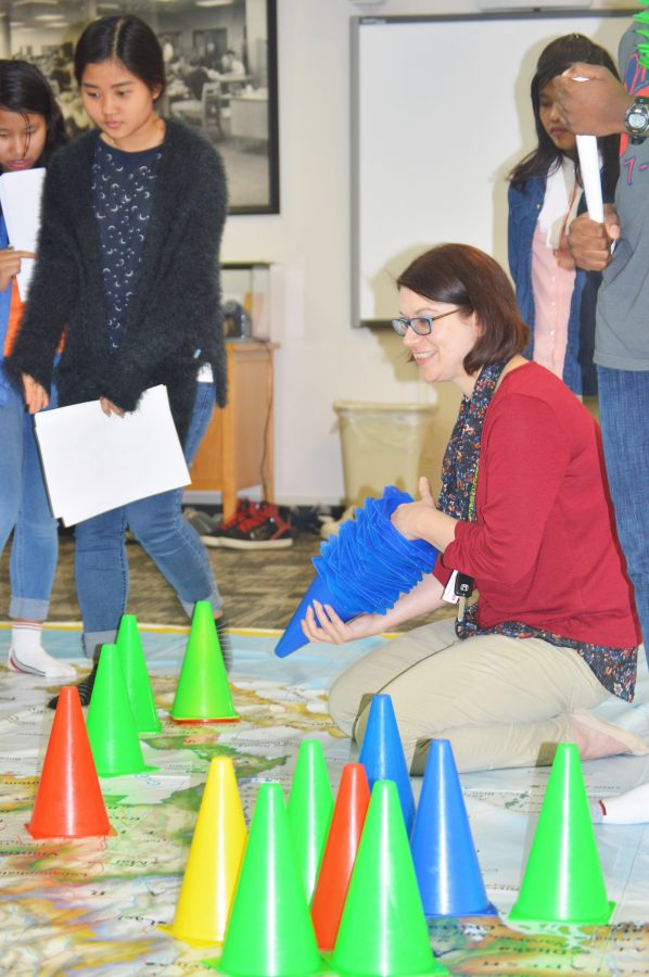 EL teacher Amy Peddie helps layout cones on her EL students' birth place. One of the first assignments for the classes to do was to put one cone where they were born and one cone on a place they would like to travel.