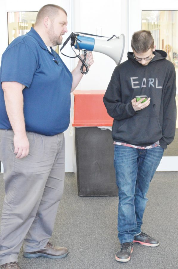 Junior Earl Evans scrolls obliviously through the Snapchat home screen as assistant principal Kirby Schott scolds him through his megaphone. After this picture was taken, Schott proceeded to throw Evans's phone in the trash, causing Evans to faint.