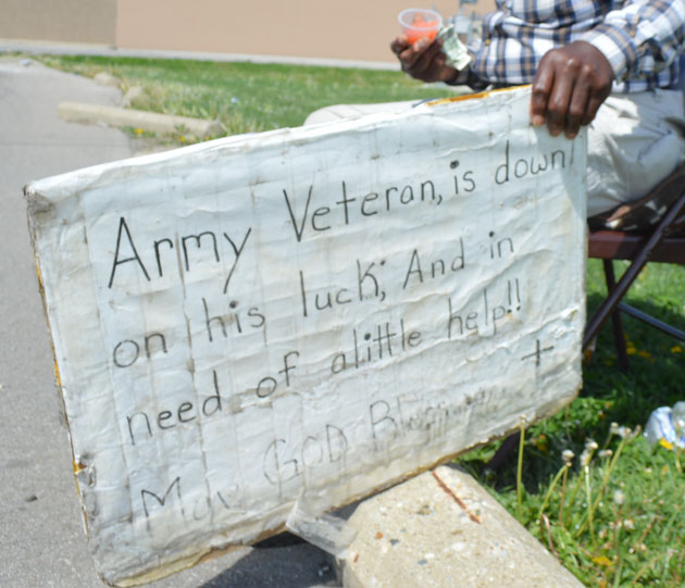 "Local impoverished veteran Arnell sits on a side street that leads to Walmart on April 18 holding a sign that reads, ""Army Veteran, is down on his luck; And in need of a little help!! May God Bless you."" He says fighting in the military left him partially deaf and disabled, prohibiting him to stand longer than a few minutes at a time."