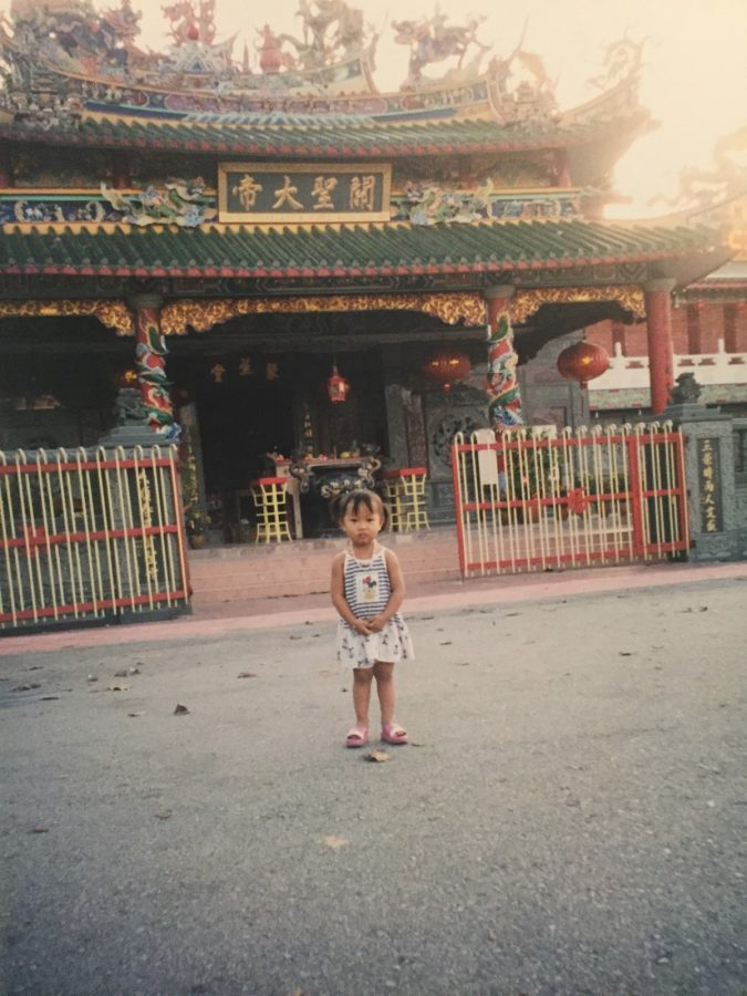 Junior Dawt Hlei poses in front of her Chinese school in Malaysia. She was 4 years old when the photo was taken.