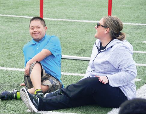 Sophomore Abel Tajonar (left) and teacher Holly Ellis (right) stretch their legs during a practice.  This is the first year that SHS has fielded a unified track team.