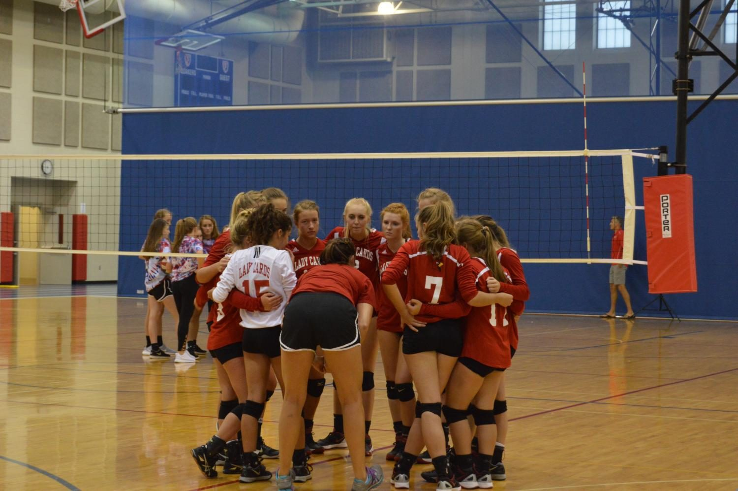 The volleyball team huddles together during a scrimmage against Plainfield High School.