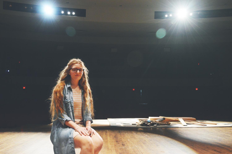 Senior Samantha Beckham sits on the auditorium stage.