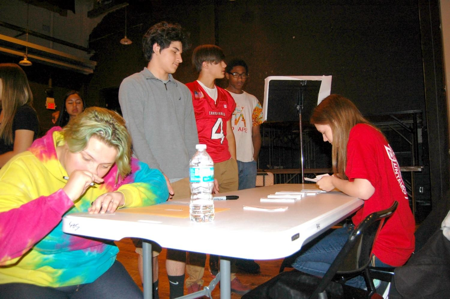 Students locate their name cards in the auditorium for picture day on Friday, Aug. 25.