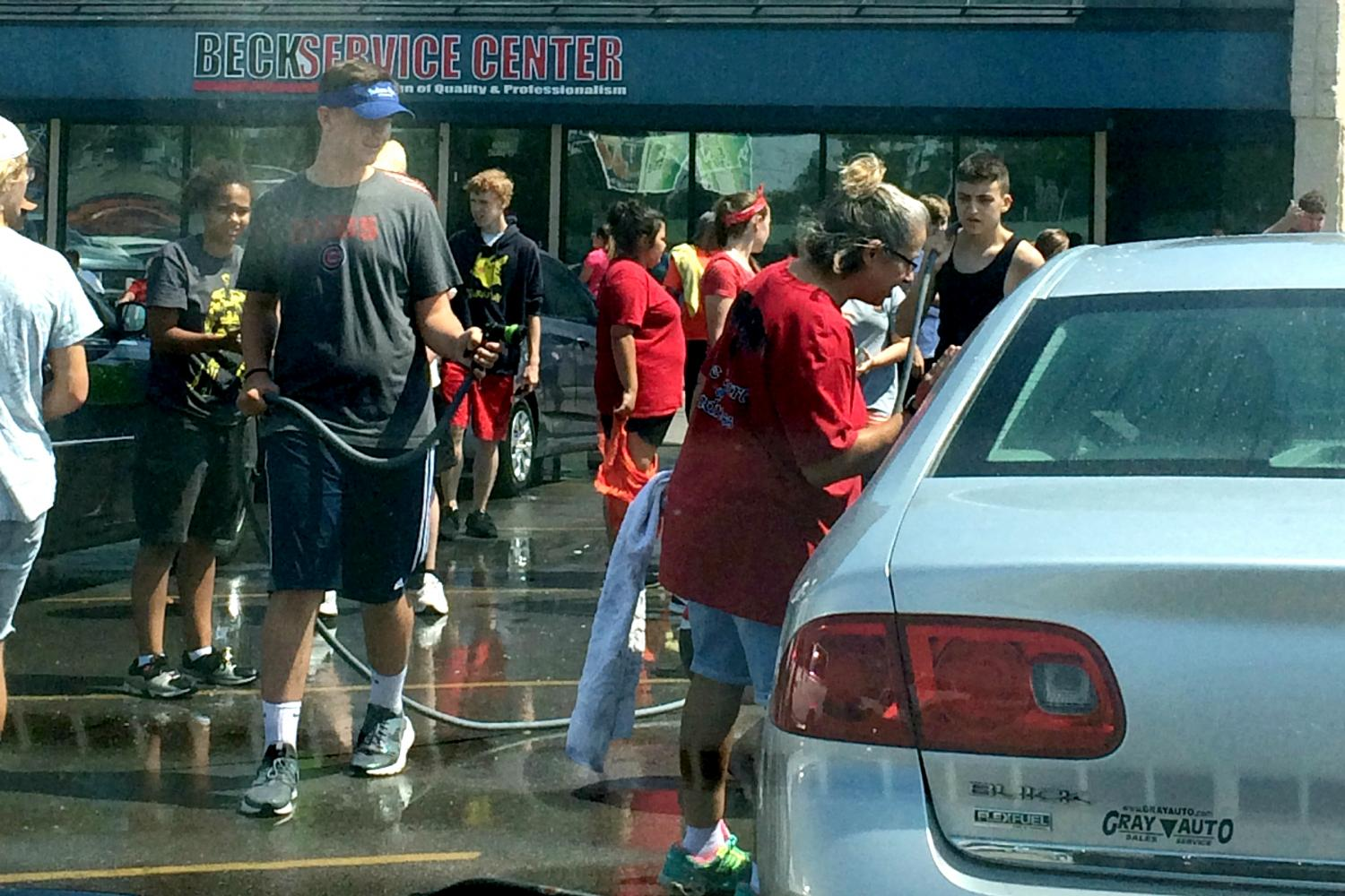 Junior Max McClellan holds a hose at the marching band car wash fundraiser on Saturday, Aug. 26.