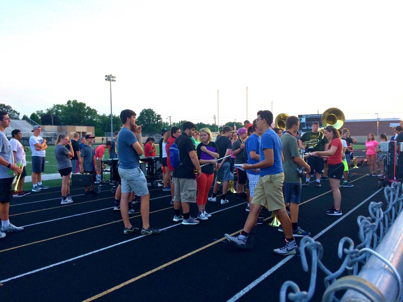 The marching band gathers at the end of rehearsal to talk about fundraising on Thursday, Aug 3.