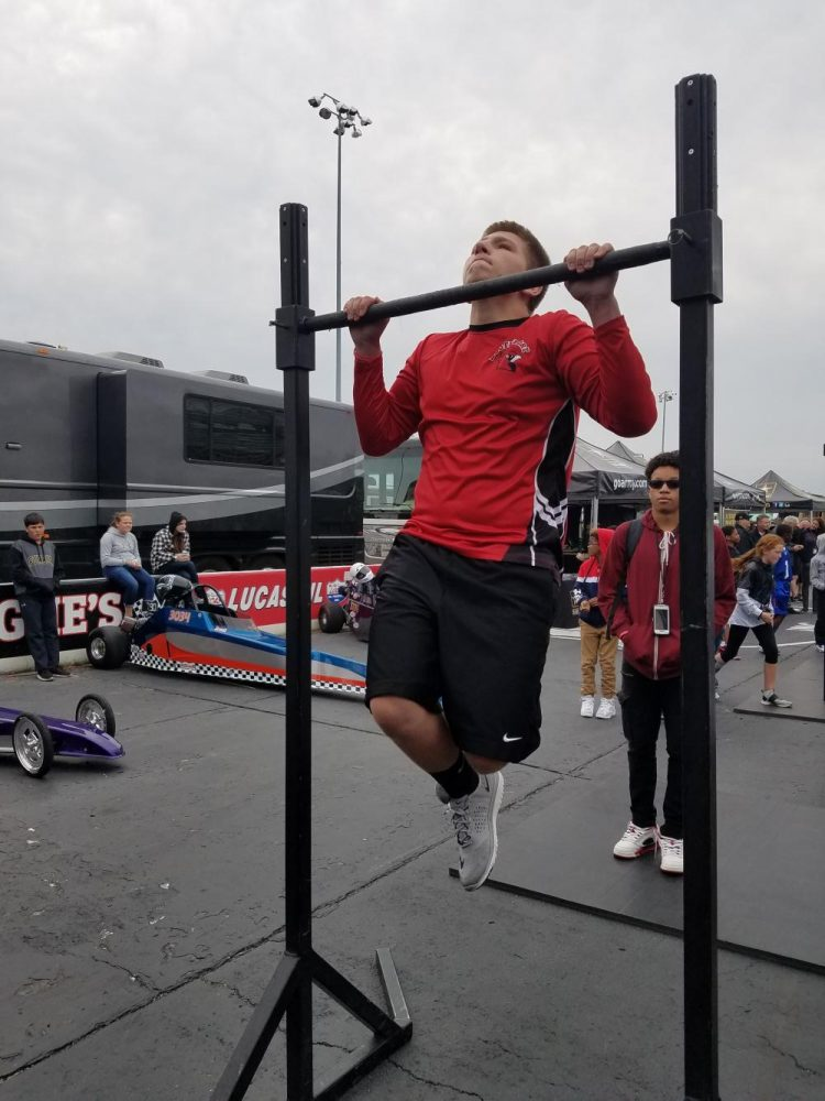 Junior Jaeden Battista does pull-ups at the Lucas Oil Raceway.