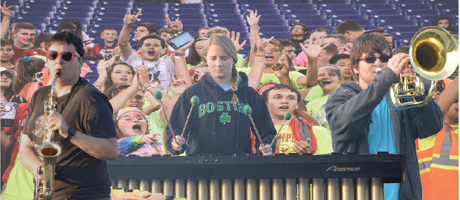 Juniors Sax O'Phone, Mary Imba, and Eupho Nium perform with the rest of the Marching Cards as the student section cheers them on. The students proceeded to swarm the field and storm after the band as they were leaving.