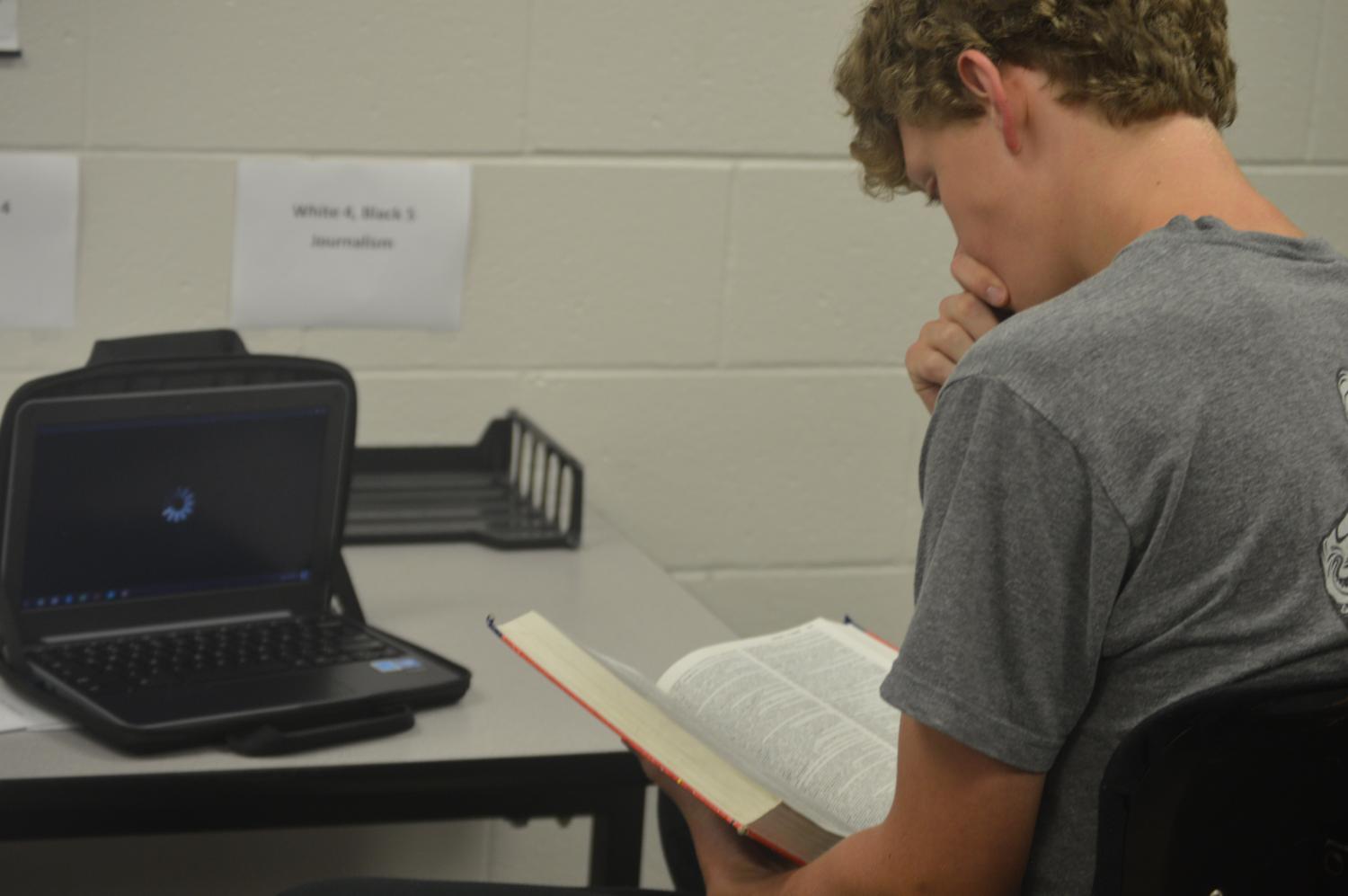 Senior Ethan Vanhalen II resorts to reading the dictionary as Bloons Tower Defense 5 struggles to load on his chromebook.