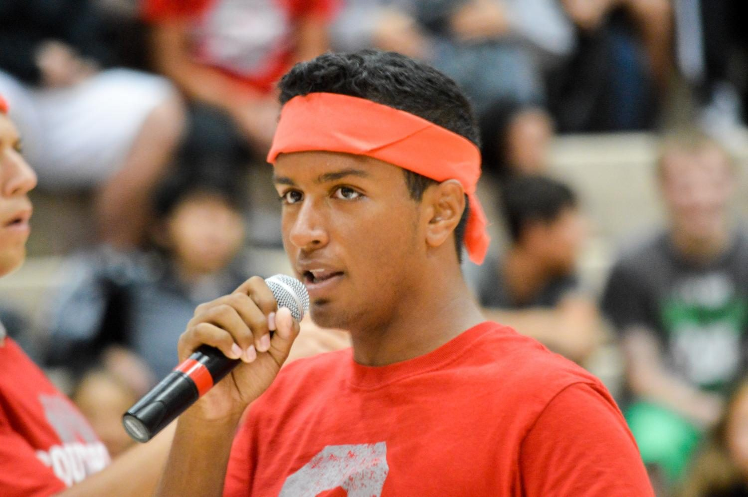 Senior+and+booster+club+officer+Seejay+Patel+speaks+through+the+microphone+to+the+student+audience+at+the+year%27s+first+pep+session.+