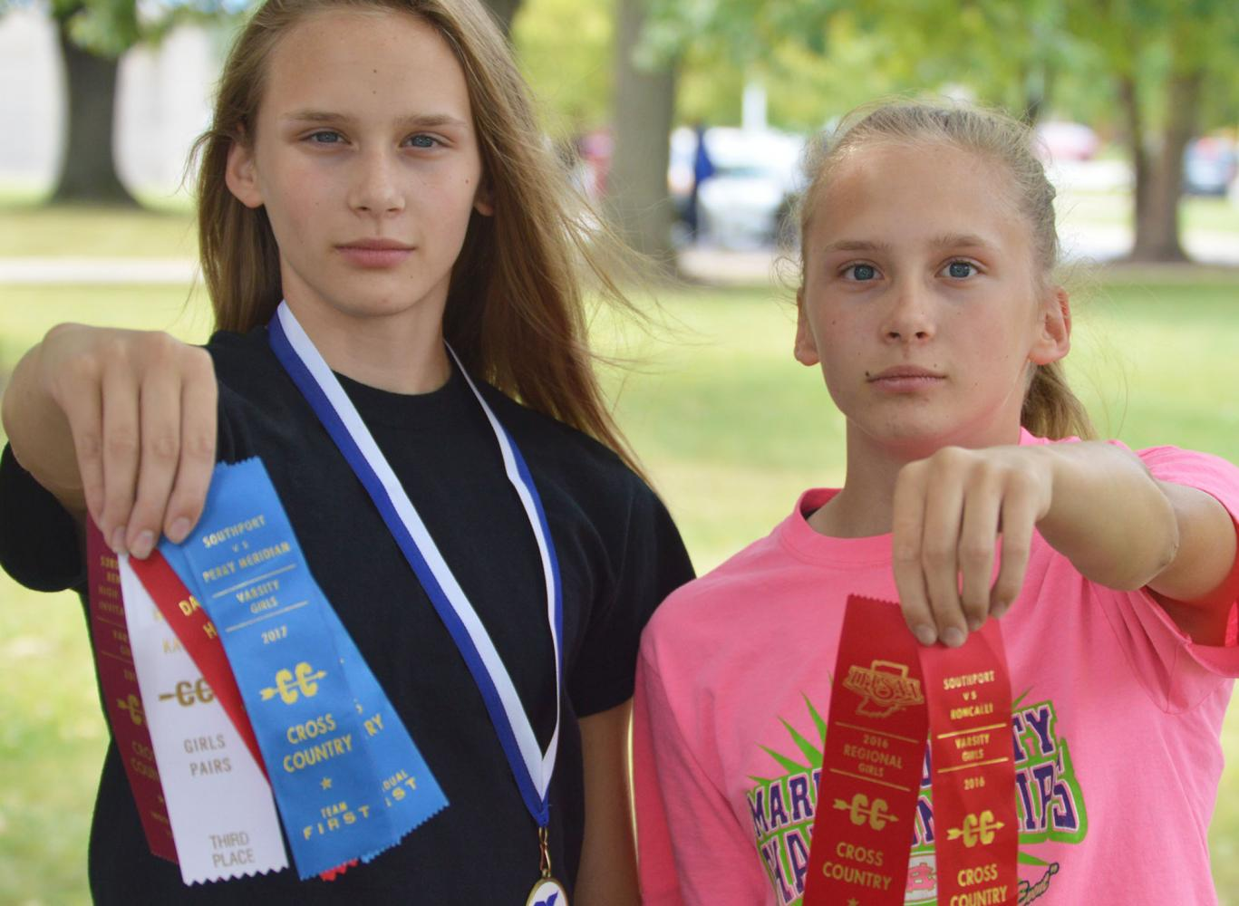 Lexie (left) and Bella (right) Green hold up ribbons they have won in cross country.