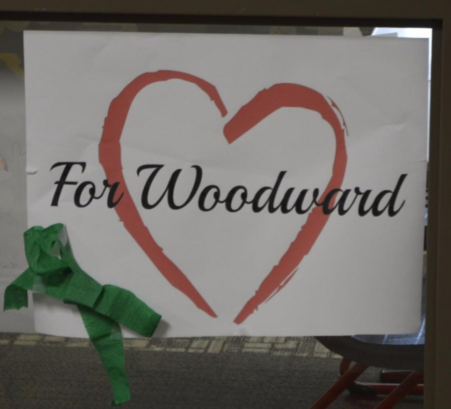 A sign in honor of Woodward hangs on one of her classroom windows. Her favorite color was green, which is the reasoning for the ribbon.