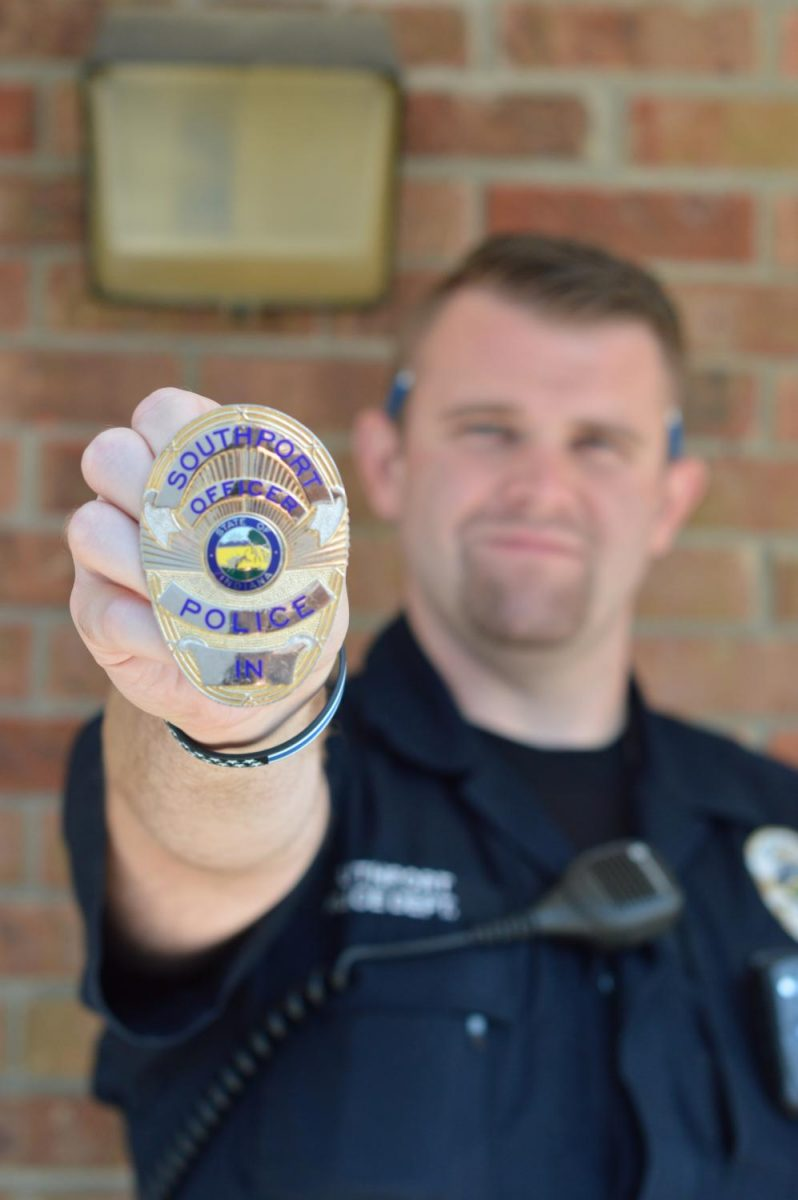 Officer+Vaughn+holds+his+newest+badge.+He+recently+moved+from+SHS+to+Southport+Police+Department+to+work.+