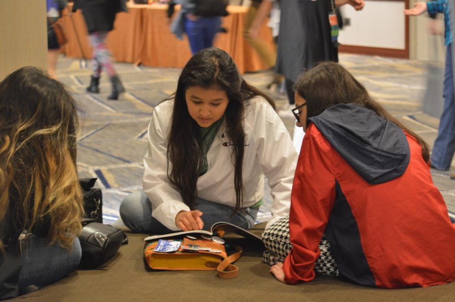 Gonzalez High School senior Jaslyn Solis reads the National High School Journalism Convention program guide with her classmates in Dallas, Texas on Nov. 17.