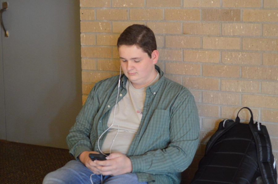 Nathan Miller sits in the lobby outside the auditorium. Due to the recent hall monitor policy, he is no longer able to.